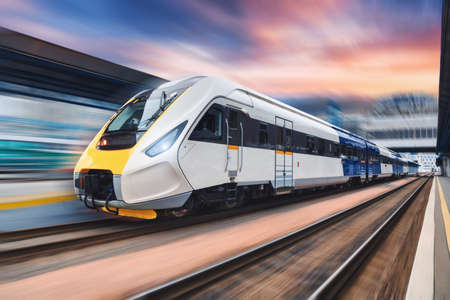 Photo pour High speed train in motion on the railway station at sunset. Modern intercity passenger train with motion blur effect on the railway platform. Industrial. Railroad transportation in Europe. Industry - image libre de droit