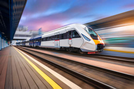Photo for High speed train in motion on the railway station at sunset. Fast moving modern passenger train on railway platform. Railroad with motion blur effect. Commercial transportation. Front view. Concept - Royalty Free Image