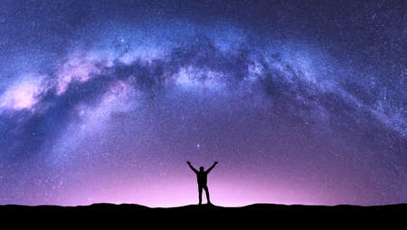 Photo for Arched Milky Way and happy man at night. Silhouette of guy with raised up arm on the hill, purple sky with stars, pink light in summer. Galaxy. Space background. Landscape with milky way arch. Travel - Royalty Free Image