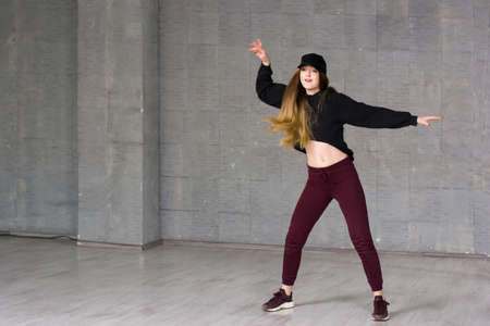 Female modern style dancer in motion. Young beautiful athletic woman dancing modern style dance hip-hop on studio on wall background.