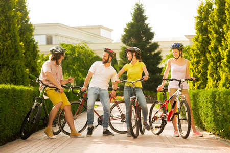 Photo for Group of joyful people with bicycles outside. Four cheerful friends spending time together outdoors. Weekend of best friends. - Royalty Free Image