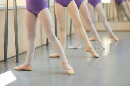 Legs of young ballerinas in ballet class. Ballet dancers in dance position near barre, focus on first girl.