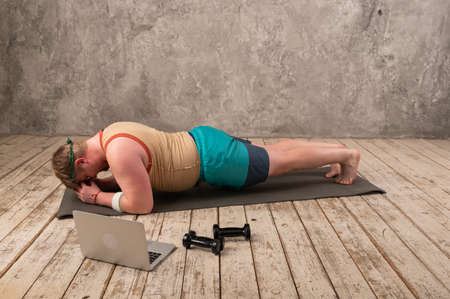 Photo for overweight man exercising, doing stretching exercises on yoga mat, watching fitness videos online on laptop at home. yoga exercises online with laptop - Royalty Free Image
