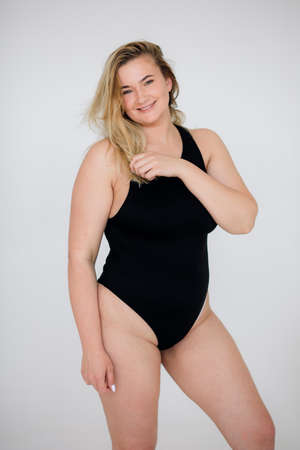 Photo pour Beautiful overweight woman in black swimsuit on white background - image libre de droit