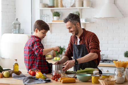 Photo pour Happy father and adorable son prepare water for cooking pasta. Smiling dad holding pan. Kid sitting on table. Ingredients for making dinner on table. Home kitchen interior. Parenthood and childhood - image libre de droit