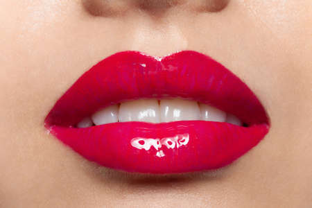 Photo pour Female plump lips with red glossy lipstick closeup macro shot. Glamor fashion sensual makeup. Magenta women mouth with white teeth. Beauty, visage and cosmetics. Self-care and cosmetology - image libre de droit