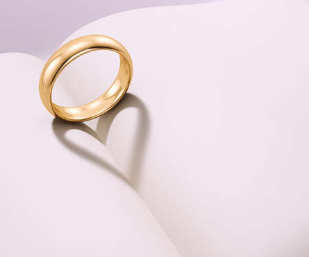 Photo pour Wedding ring casting heart shaped shadow over a blank book - image libre de droit