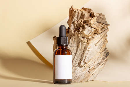 Photo pour Glass cosmetic bottles with a dropper stand next to a log on a beige background with bright sunlight. The concept of natural cosmetics, natural essential oil. - image libre de droit