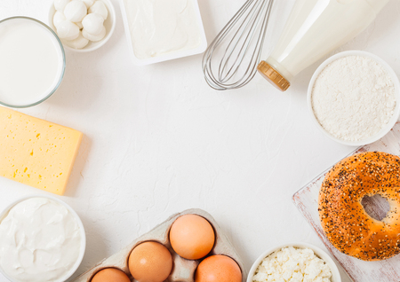 Fresh dairy products on white table background. Glass of milk, bowl of sour cream and cottage cheese and eggs. Fresh baked bagel. Steel whisk. Top view.
