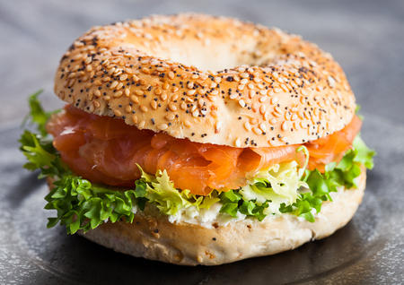 Foto de Fresh healthy bagel sandwich with salmon, ricotta and lettuce in black plate on dark kitchen table background. - Imagen libre de derechos