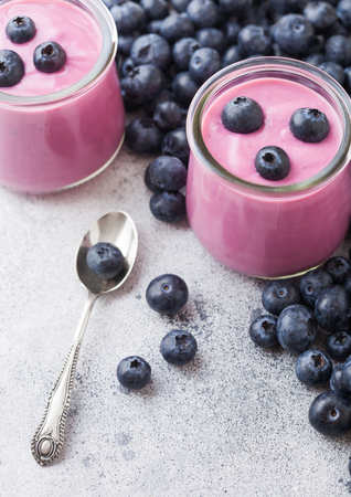 Fresh homemade creamy blueberry yoghurt with fresh blueberries and silver spoon on stone table background