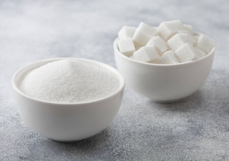 Photo pour White bowl plates of natural white sugar cubes and refined sugar on light background. Top view - image libre de droit