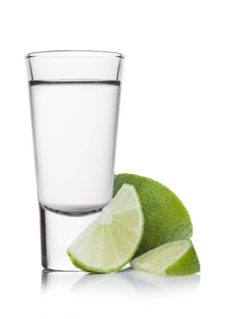 Glass shot of silver tequila with lime slices on white background.