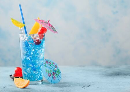 Foto de summer cocktail in highball glass with sweet cocktail cherries and orange slice with umbrella on blue table background. Space for text - Imagen libre de derechos