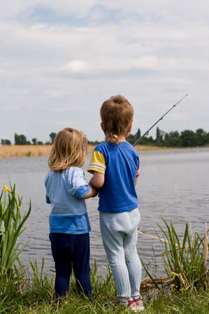 Little boy and girl fishing on the lake