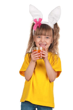 Portrait of happy little girl with carrot juice over white background