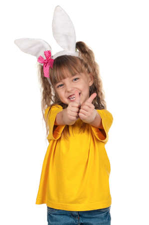 Portrait of happy little girl with bunny ears giving you thumbs up over white background.
