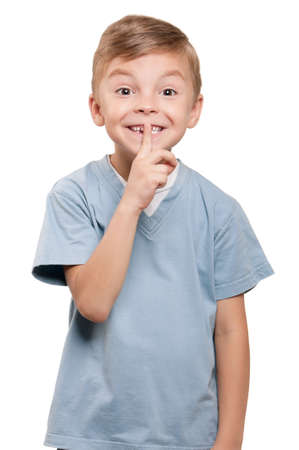 Portrait of beautiful little boy with silence gesture over white background