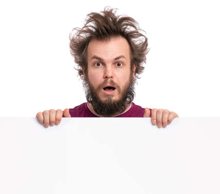 Foto de Crazy bearded Man with funny Haircut showing empty blank signboard with copy space. Guy with surprised eyes and mouth open peeking out from behind big white banner, isolated on white background. - Imagen libre de derechos