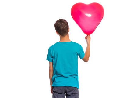 Foto de Back view. Portrait of teen boy holds red heart shaped balloon, isolated on white background. - Imagen libre de derechos