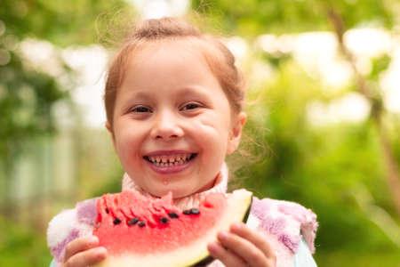 Photo pour cute little girl eating watermelon on the grass in summertime - image libre de droit