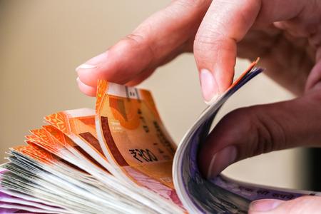Photo pour Woman's hands holding brand new indian 100, 200, 500, 2000 rupees banknotes. - image libre de droit