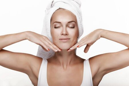Photo pour A beautiful young girl in a white blouse with a towel on her head, after a shower, applies cream to her face, makes a massage and laughs. Moistens a face with cream. Spa. In the studio on a white background. - image libre de droit