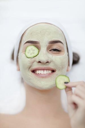 Photo pour Beautiful young woman receiving facial mask of cucumber in beauty - image libre de droit