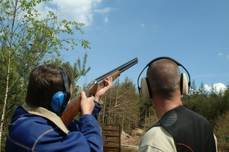Man shooting clay pigeons being instructed