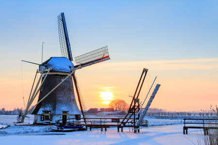 Beautiful dutch windmill near Baambrugge in the Netherlands covered in snow with ice on the river at sunset