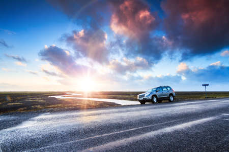 A car on the road at sunrise in the beautiful volcanic landscape of Myrdalssandur in the southern part of Iceland in winter