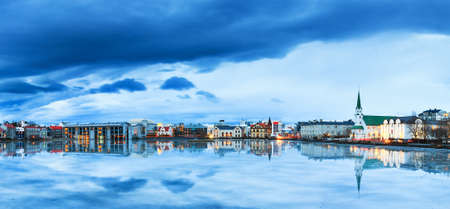 Beautiful panorama of the skyline cityscape of Reykjavik, reflected in lake Tjornin at the blue hour in winter