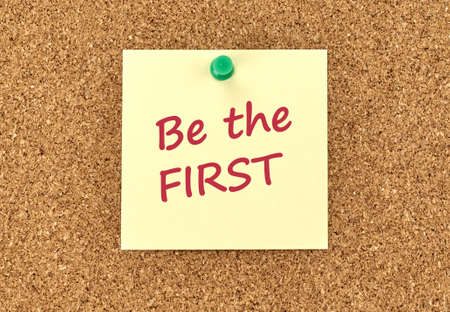 Photo pour The phrase Be The First in red text on a yellow sticky note posted to a cork notice board. - image libre de droit