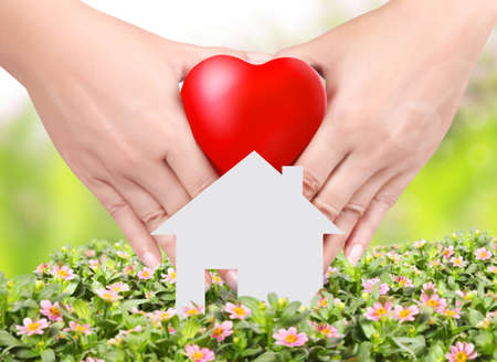 Heart in a hands  floral background and home