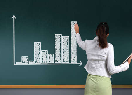 Business woman showing charts on the blackboard