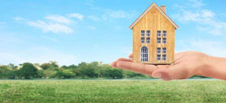 Photo pour Mortgage concept by money house. holding a house model in hand - image libre de droit