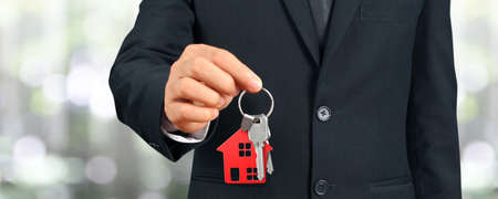 Photo pour Real estate agent handing over a house keys in hand - image libre de droit
