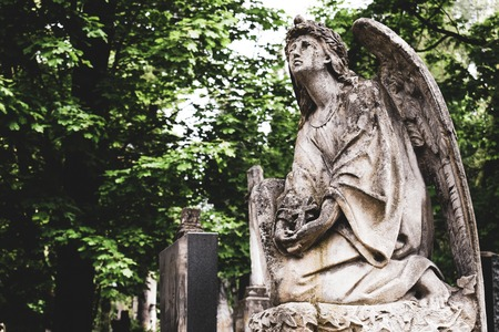 Obsolete old stature of angel with cross on burial on cemetery in Lychakiv Cemetery, Lviv.