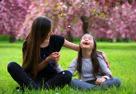 Foto de Happy beautiful young woman with girl in blossom park with trees and flowers. - Imagen libre de derechos