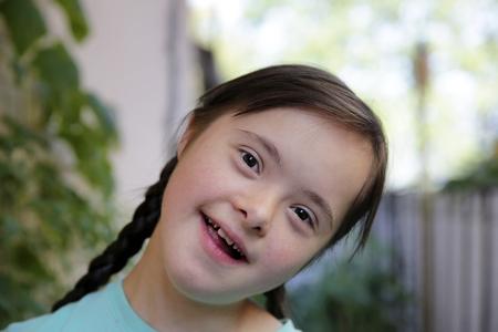 Photo pour Portrait of little girl smiling in the garden - image libre de droit