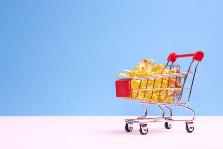 Shopping trolley with pills and drugs on a blue background. Conceptually for healthcare, hospital, clinic and medical business.