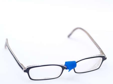 broken eyeglasses provisorily repaired with blue tape