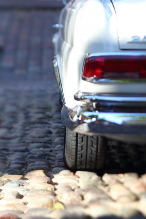 selective focus photo of white vintage car on cobblestone pavement