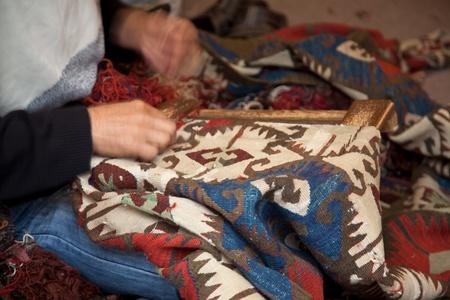 Man  weaving a carpet