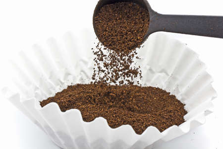 Pouring ground coffee into a paper filter with a plastic scoop