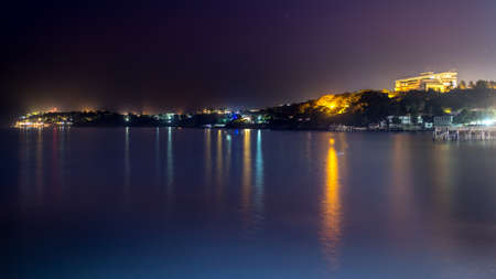 The still waters of the Atlantic ocean reflecting the colourful lights along the shores of downtown Dakar
