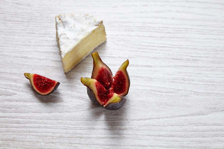 Camembert piece with splitted figs on whte wooden table