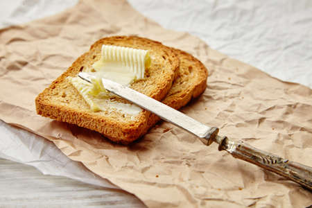 Roasted toasts with butter for breakfast on craft paper, antique knife