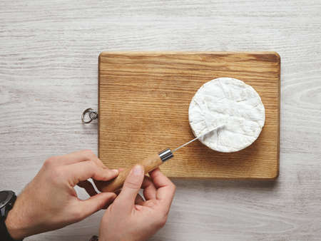 Top view brutal beautiful man hands accurately cut a triangle piece of camembert cheese with antic knife on cutting board isolated on whithe aged brushed wooden table