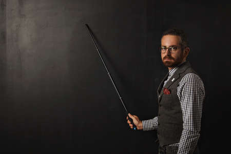 Serious bearded professor in plaid shirt and tweed vest, wearing glasses and looking condemn on camera, shows something on school black board with his pointer